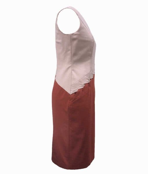 Side view of a beige and burnt orange princess line dress with a braid running diagonally on the front from the hip to waist.