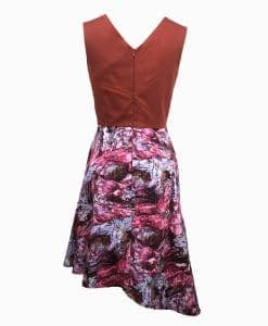 Back view of a burnt orange top above the waist with architectural lines and a wookey hole cave print skirt that is asymmetrically longer on the left side.