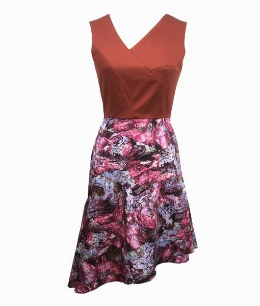 Front view of a burnt orange top above the waist with architectural lines and a wookey hole cave print skirt that is asymmetrically longer on the left side.