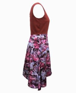 Side view of dress with a burnt orange top above the waist and wookey hole cave print skirt that is asymmetrically longer on the left side.