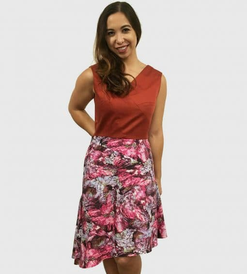 Woman in dress with a burnt orange top above the waist with architectural lines and a wookey hole cave print skirt that is asymmetrically longer on the left side.